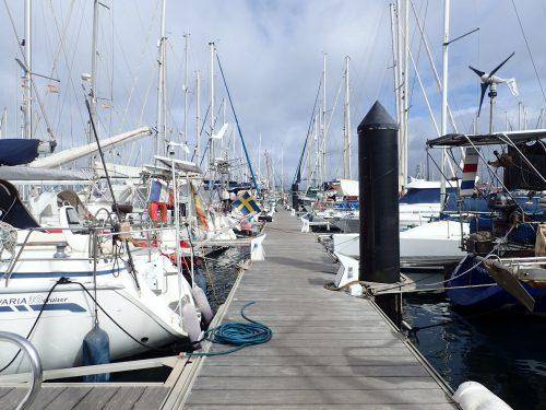 """I Las Palmas hade vi lyckats få en plats på """"jollebryggan"""", det är bryggan som hör till seglarskorna. I själva kommunala marinan var det fullt, och även på båtklubbsbryggan. Här vajar några svenska flaggor, vi har trevliga båtgrannar."""